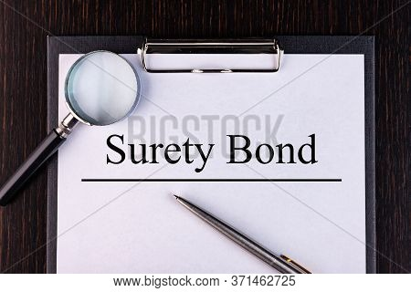 Text Surety Bond Is Written On A Notebook With A Pen And A Magnifying Glass Lying On The Table. Busi