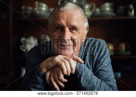 Elderly Man With Walking Stick Sitting At Home. Portrait Of Old Man In 80s Years.