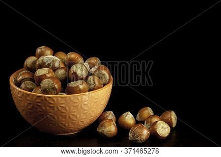 Orange Color Bowl With Hazelnuts And Hazelnuts On Table
