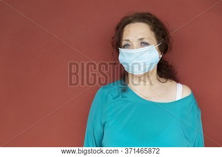 Portrait Of Old Woman With Protective Face Mask On Red Wall. Confinement By Coronavirus. Covid-19 Co