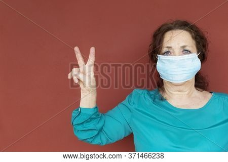 Portrait Of Old Woman With Protective Face Mask Making Victory Sign With Her Hand On Red Wall. Confi