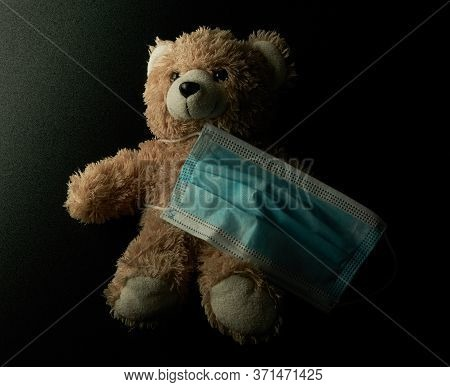 Teddy Bear With A Medical Mask In Darkness. Chilhood Preventing Covid-19.