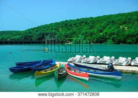 Water Tourist Rental Business On The Lake. Large Assortment Of Boats In The Turquoise Lagoon. Kayaks