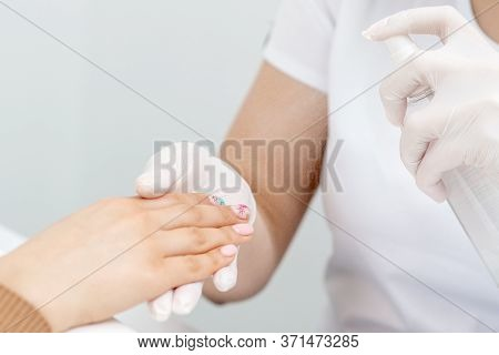 Close Up Of Manicurist Moisturising Fingernails Of Woman By Thermal Water.