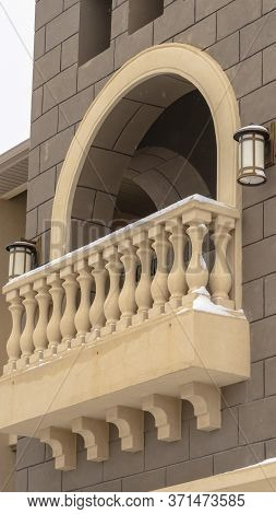 Vertical Crop Exterior Of Apartment With Moulded White Balustrade On The Arched Balcony