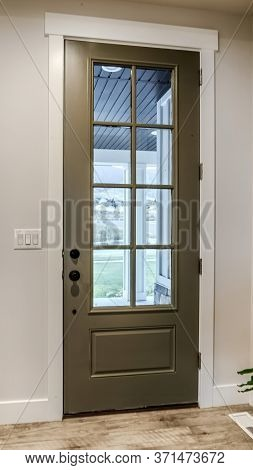 Vertical Hinged Front Door With Glass Pane Viewed From Interior Of Home With Wood Floor