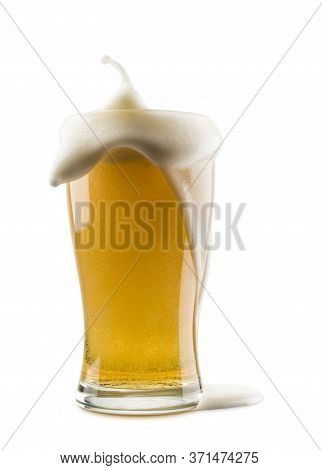 Glass Of Lager Beer With Overflowing Foam On White Background