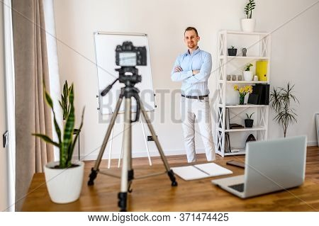 Business Coach, Mentor. A Young Guy Is Recording Business Vlogs, He Is Standing Near A Flip Chart Wi