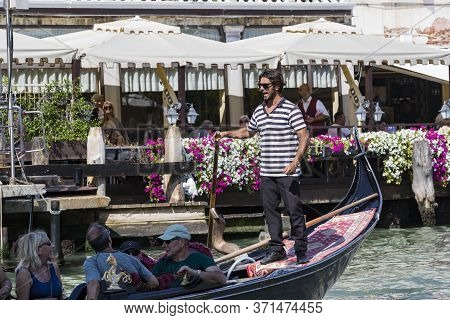 Italy, Venice - 5 September, 2018: Men Gondoliers Drive Gondolas With Tourists In Venice In Italy.