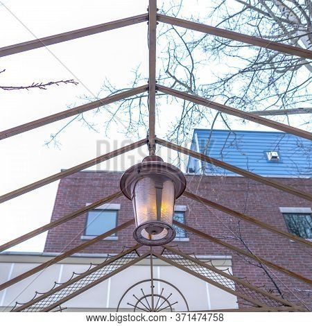 Square Vintage Outdoor Lamp Hanging On The Gable Metal Roof Frame Of A Pergola