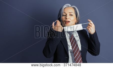 Business Woman Removes Protective Mask From Her Face. Focus On Female Face. Mature Woman In Formalwe
