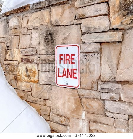 Square Fire Lane Sign On Stone Retaining Wall Amid Thick Fresh Snow On A Hill In Winter