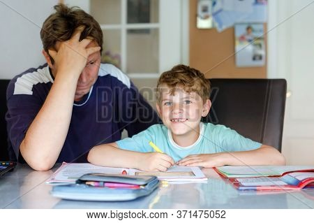 Cute Little School Kid Boy At Home Making Homework With Dad. Child Writing, Father Helping Him, Duri