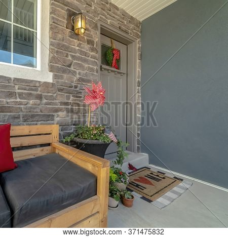 Square Crop Wooden Bench With Pillows At The Porch Of Home With Glass Paned Gray Front Door