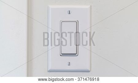 Panorama Crop Electrical Rocker Light Switch With Flat Broad Lever On White Interior Wall