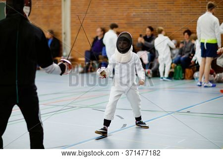 Little Kid Boy Fencing On A Fence Competition. Child In White Fencer Uniform With Mask And Sabre. Ac