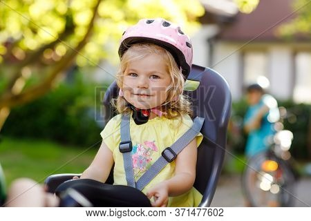 Portrait Of Little Toddler Girl With Security Helmet On The Head Sitting In Bike Seat Of Parents. Bo