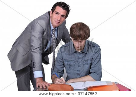 Teacher helping male teenager