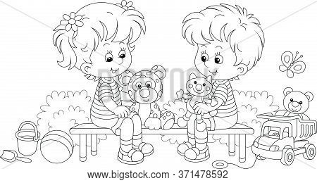 Cheerful Small Children Sitting On A Bench, Talking And Playing With Their Funny Toys On A Summer Pl