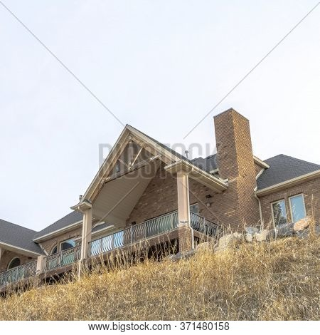 Square Crop Hill Top Home Exterior Featuring Stone Brick Wall And Gable Roofs Over Balcony