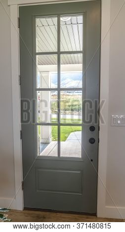 Vertical Crop Front Door With Balck Knob And Glass Panes Against White Wall And Wood Floor