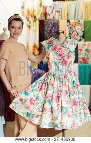 Pretty Young Girl Adjusts Dress On The Mannequin. Flower Dress On A Mannequin. Seamstress In A Sewin