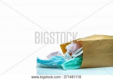 Used Surgical Face Mask In Brown Paper Bag Isolated On White Background. Medical Waste. Infectious W