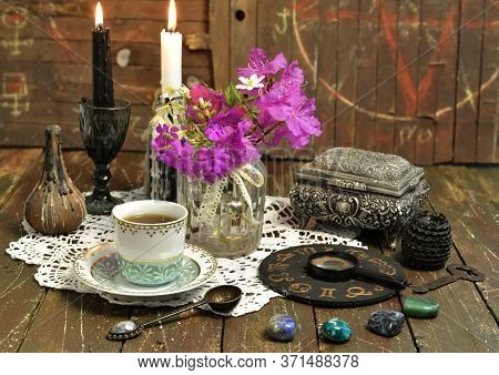 Still Life With Zodiac Chart, Black Candle, Cup And Stones. Esoteric, Wicca And Occult Background Wi
