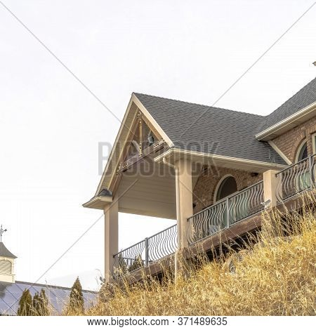 Square Crop Hill Home With Gable Roof Over Balcony And Porch Against Cloudy Sky Background