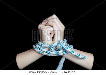 Bound Female Hands Pulling A Rope On A Black Isolated Background. Close-up, Selective Focus, Low Key