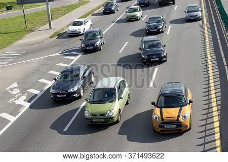 Many Multi-colored Passenger Cars Ride On The Ring Road Of A Multi-lane Freeway. Flow Of Cars. Top V
