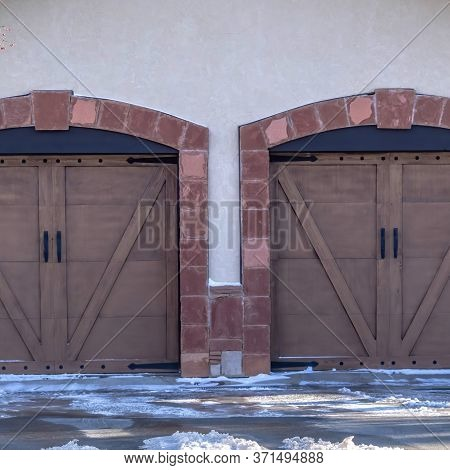 Square Facade Of A Residential Garage With Gable Roof And Two Hinged Wooden Doors