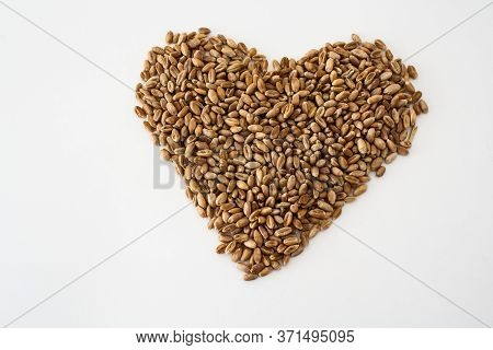 Wheat Grains Laid Out In The Shape Of A Heart On A White Background, Natural Dried Grains In The Cen