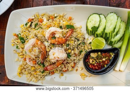 Top View Of Fried Rice With Shrimp, Lemon, Cucumber, Onion And Chili Fish Sauce In White Plate.