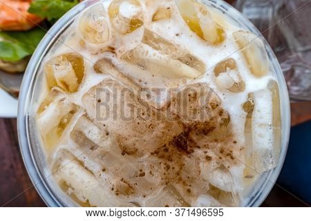 Top View Of Iced Coffee With Milk In Plastic Cup On Wooden Table.