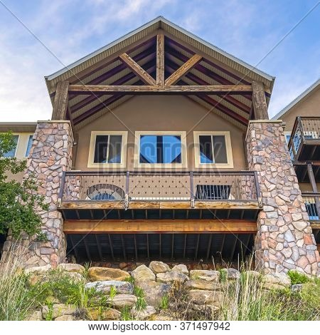 Square Crop Gable Roof With Wooden Beams Over Balcony And Porch With Square Stone Columns