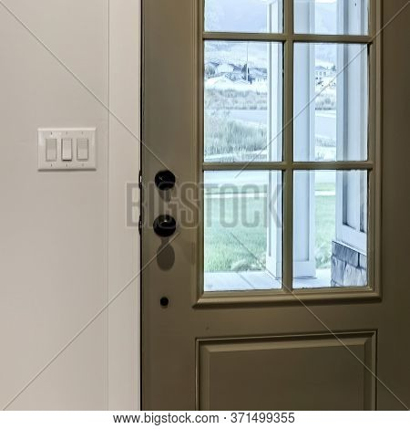 Square Crop Hinged Front Door With Glass Pane Viewed From Interior Of Home With Wood Floor