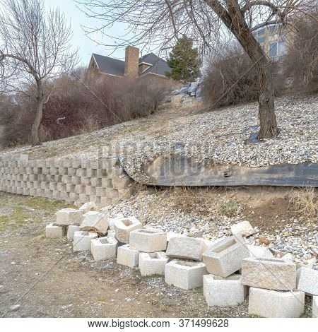 Square Frame Stone Blocks Of Collapsed Retaining Wall Holding The Soil Of A Slope With Houses