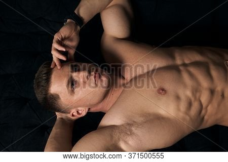 Muscular Guy Is Lying On The Couch.
