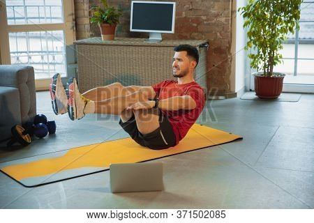 Crunches. Young Caucasian Man Training At Home During Quarantine Of Coronavirus Outbreak, Doing Exer