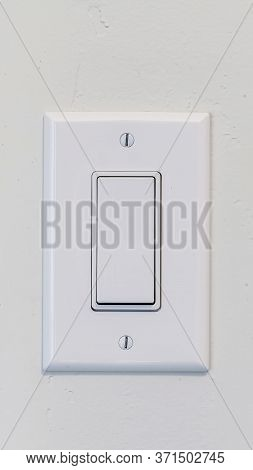 Vertical Electrical Rocker Light Switch With Flat Broad Lever On White Interior Wall