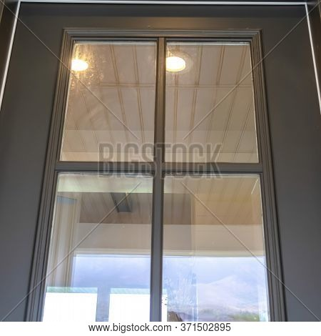 Square Wooden Front Door Of Home With Glass Panes That Reflects The Outdoor View