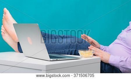 Close-up Of Male Legs On A Desktop Near A Laptop. The Concept Of Boredom And Fatigue At Work
