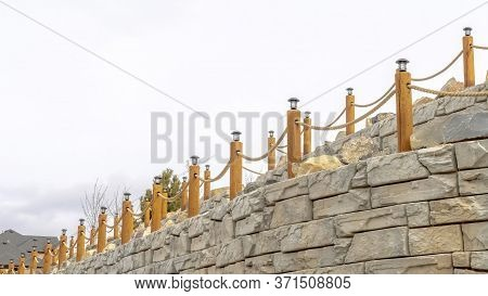 Panorama Crop Rope Fence With Lamps On Posts Lining A Retaining Wall Made Of Stone Blocks