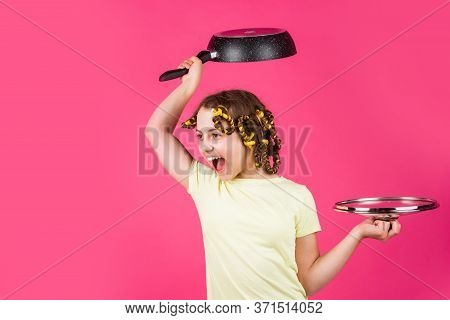 Express Real Emotions. Cute Funny Little Girl Wearing The Curler And With The Pan. Small Girl Housew
