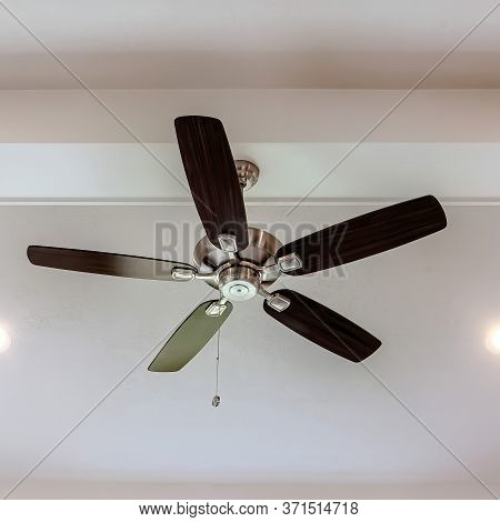 Square Ceiling Fan With Wood Blades And Built In Lights On The Ceiling Beam Of Home