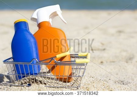 Two Bottles Of Sunscreen Lotion Or Cream With Spf On The Sandy Beach In A Small Metal Yellow Shoppin