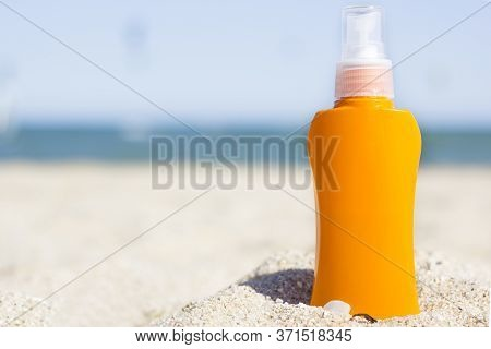 Orange Sunscreen Cream Bottle On The Beach. Summer Time On The Beach With Sunblock. Sea And Blue Sky