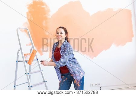 Dancing Funny Young Woman Painting Interior Wall With Paint Roller In New House. A Woman With Roller