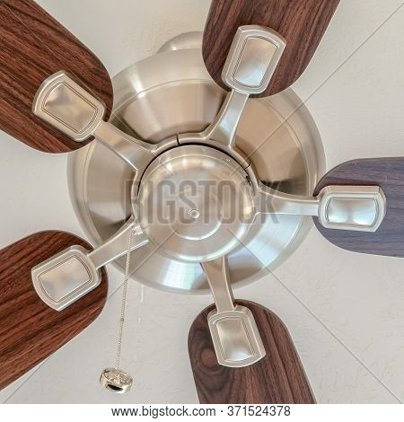 Square Crop Ceiling Fan With Wooden Blades And Lights Mounted On The Ceiling Of A Home